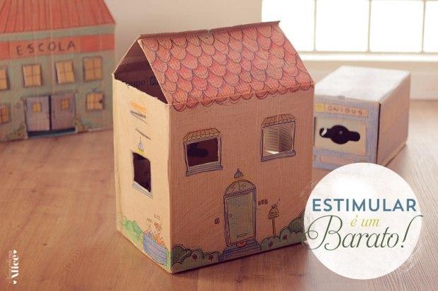 Na imagem: Foto de 3 caixas: uma com o desenho de uma casa, uma com o desenho de uma escola e uma simulando um ônibus.